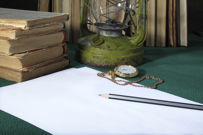 On the desktop are: a clean white sheet of paper, a simple pencil, old books, pocket watch on a gold chain and a kerosene lamp. Retro stylized photo.